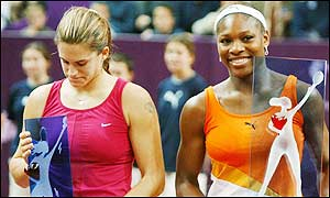 Amelie Mauresmo looks downcast while Serena Williams smiles at the trophy presentation