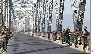 Indian soldiers on patrol on a bridge in Assam