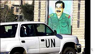 A car carrying UN inspectors drives past a portrait of Iraqi President Saddam Hussein