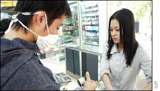 A man wearing a surgical mask in Guanzhou city buys a flu tonic