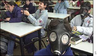 Israeli schoolchildren put on gas masks during an exercise