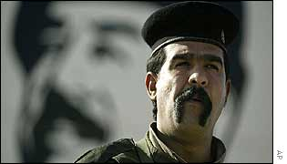 An Iraqi soldier standing in front of a poster of Saddam Hussein