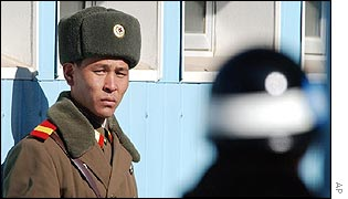 North (left) and South Korean soldiers eye each other at the border