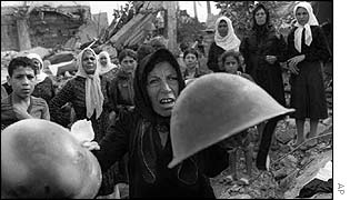 A Palestinian woman brandishes helmets during a memorial service in Beirut September 27, 1982, for victims of Lebanon's Sabra refugee camp massacre