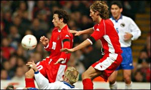 Simon Davies and Robbie Savage attempt to gain Wales possession