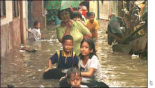 A family crosses a flooded street in Jakarta