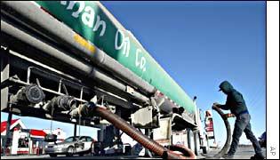 An oil  worker delivers gasoline