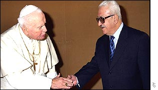 Pope John Paul shakes the bloodied hand of tyrant Saddam's deputy, Tariq Aziz, in February 2003