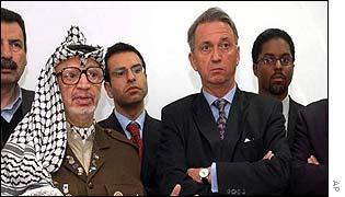 Yasser Arafat stands with UN envoy Terje Roed-Larsen