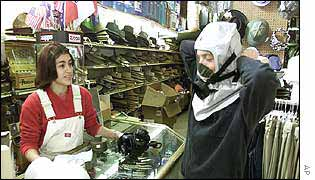 A customer tries on a gas mask
