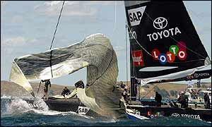 The crew struggles to contain their headsail as it whips around