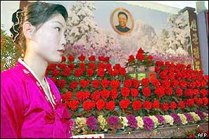 A North Korean hostess waits beside a display of the Kimjongilia flowers