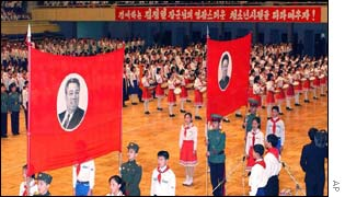 North Korean youngsters carry red flags bearing portraits of the late leader Kim Il-Sung
