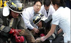Firefighters and medics move a victim to a stretcher after the South Korean subway fire