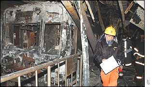 A firefighter inspects the wreckage of one of the subway carriages