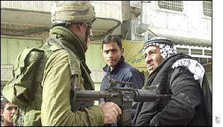 Israeli soldier points gun at Palestinian man