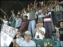 Bangladeshi and South African supporters celebrate the fall of a West Indies wicket