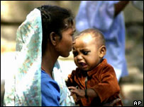 A Muslim woman and child in a refugee camp after the riots last year