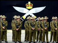 Gurkhas with the kukri logo behind them