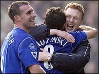 Everton manager David Moyes hugs Tomasz Radzinski as David Unsworth (left) looks on