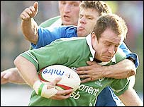 Ireland's Denis Hickie is tackled by Italian Cristian Stoica