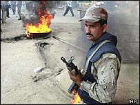 A Pakistan soldier by a burning tyre in Karachi