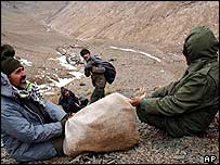 Searchers haul a body bag down the slope