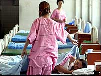 A Thai female drug addict (L) covers her friend with a blanket in Bangkok