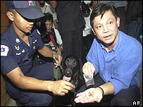 Two Thai policemen show methamphetamines after their operation to search for drugs at a slum in Bangkok