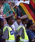 Zimbabwean police keep an eye on spectators at the match between Australia and Zimbabwe, in Bulawayo.