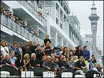 Spectators watch Switzerlands Alinghi and Team New Zealand leave Viaduct Harbour in Auckland