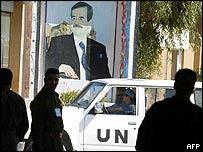 UN inspectors drive past a mural of Saddam Hussein