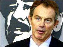 Tony Blair with Saddam portrait it background