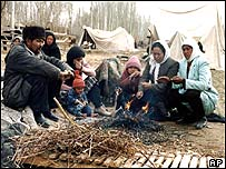 A homeless family sit around a camp fire