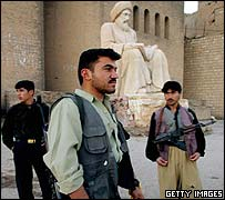 Kurdish fighters stand guard near the statue of a Kurdish poet at the gate of Erbil Castle