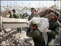 Chinese Peoples Liberation Army (PLA) soldiers clear the rubbles of a collapsed house