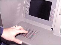 Man entering PIN number at a cash machine