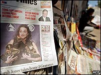 A man reads a newspaper at a roadside stall carrying a front page photo of US jazz singer Norah Jones in New Delhi