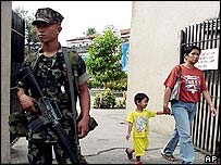 A Philippine Marine guards an entrance to a Catholic shrine in Zamboanga City on Monday February 24, 2003