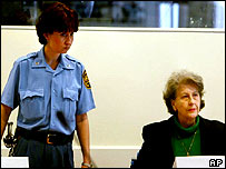 A tribunal guards stands next to Plavsic as the sentence is read out