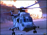 A military helicopter flies in front of a burning oil well