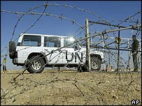 A truck carrying UN weapons inspectors enters a barbed wire- fortified gate at an Iraqi military base