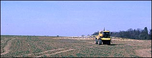 Tractor spraying crops in field