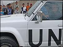 UN weapons inspectors drive by a group of Iraqi children as they enter a cigarette factory in Baghdad