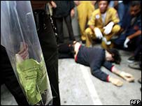 Thai police stand over body of suspect