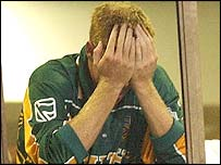 South African captain Shaun Pollock holds his head in his hands after rain stops play
