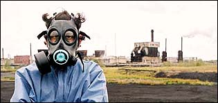 Tim Samuels in mask in front of factory