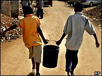 Children carry a bucket of water in Zevenfontein community outside Johannesburg