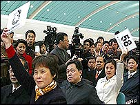 Auctioneers raise number plates at a makeshift auction site set up inside a Maglev station in Shanghai