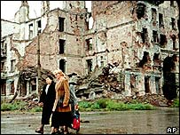 Chechen women walk past destroyed buildings